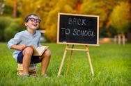 Cute little schoolboy reading book Stock Photos