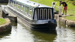 Caen Hill Canal Locks.  Tight top shot as boat leaves gates - stock footage