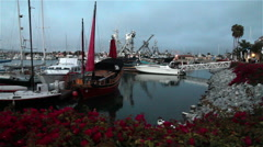 Beautiful bougainvillea flowers and red sails in harbor at evening Stock Footage