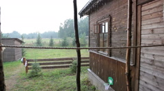 Strong rain and wooden house with verand in village Stock Footage