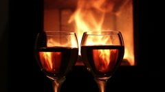 Wine glasses in front of fireplace fire Stock Footage