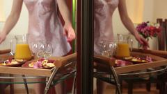 Woman in nightdress taking tray with breakfast from table Stock Footage