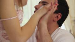 Seductive female in lingerie kisses and undresses boyfriend - stock footage