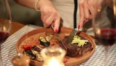 Pretty woman cutting grilled steak with knife in restaurant Stock Footage