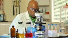 Laboratory technician looking in a microcope and taking notes 4k Stock Footage