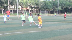 Asian boys playing football on the court Stock Footage