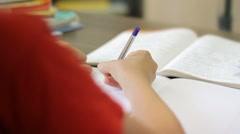 Smart pupil doing homework at home, textbooks, close-up, studying Stock Footage