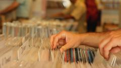 Customers browsing through vintage records in records store - stock footage