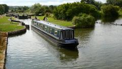 Caen Hill Canal Locks. Wide shot as a boat leaves a lock Stock Footage