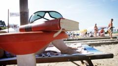 Kirja ja aurinkolasit rannalla Arkistovideo