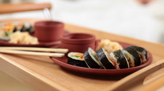 Female carrying tray with delicious Japanese sushi rolls to bed, click for HD Stock Footage