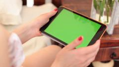 Woman using tablet computer, scrolling pages on green screen, click for HD - stock footage