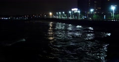 4k video,Night Ocean waves,traffic & urban building at night. Stock Footage