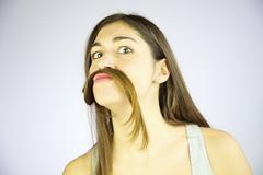 funny girl doing moustache with long hair - stock photo