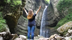 A young girl receives energy from the beautiful waterfall falling off a cliff Stock Footage