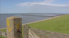 Sea dike, Wadden Sea and mudflats + pan Wierum village behind dike Stock Footage