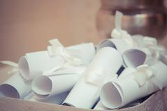 creative invitations are roll up in the scrolls. - stock photo