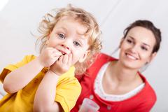 eating child with mother behind - stock photo