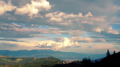 Clouds forming over sunset mountain tops Stock Footage