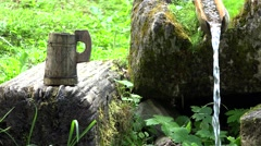 Traditional rustic wooden cup of water near a pure mountain water spring 4K Stock Footage