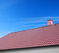 roof with brown tiles on a background of blue sky, new roof - stock photo