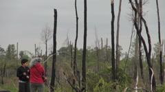 Virginia wetland blackened tree trunks and two people Stock Footage