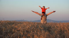 Father and son game, parent giving piggyback ride in wheat culture at sunset 4K Stock Footage