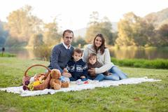 Adorable young family of four, having picnic on a sunny day Stock Photos