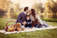 adorable young family of four, having picnic on a sunny day - stock photo
