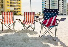 Three folding beach chairs under shade on beach Stock Photos