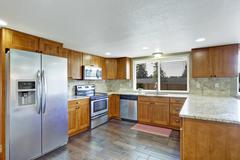 kitchen with granite tops and tile back splash trim - stock photo