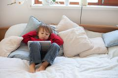 Adorable cute baby boy, playing on tablet in bed Stock Photos