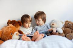 two boys, reading a book, educating themselves - stock photo