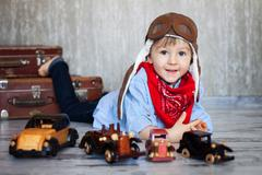 Little boy, playing with wooden cars, indoor, suitcases behind him Stock Photos