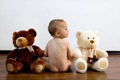 Cute naked boy with teddy bears Stock Photos