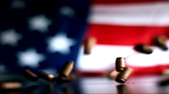 Slow Motion 9mm Bullet Shells dropping in front of american flag Stock Footage