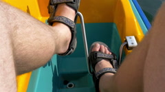 A mans feet paddling the water bicyle Stock Footage