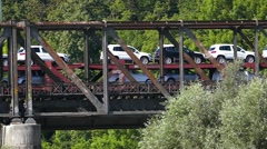 Slow Motion Freight Train transporting New Car Auto Cargo over Old Metal Bridge Stock Footage