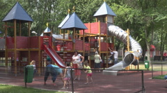 Boys in toy castle at playground use a slide, girls with moms play girlie games Stock Footage
