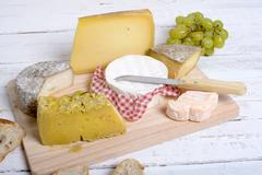 assortment of french cheeses and seasonal fruit - stock photo