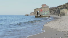 Bomb shelter with graffiti on shore of baltic sea - zoom out - stock footage