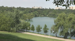 PAN shot over green park inside big city, tall buildings background, lake view Stock Footage