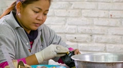Siem reap, cambodia - circa dec 2013: woman polishes enamel cup in souvenir w Stock Footage