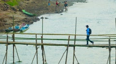 Luang prabang, laos - circa dec 2013: bamboo bridge over a small river. conve Stock Footage