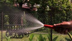 Watering Hose, Man refreshes lawn with a garden hose, close up shot - stock footage
