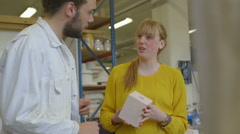 Female and male artists talking in ceramic workshop Stock Footage