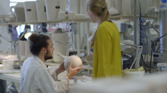 Male potter teaching pottery to woman Stock Footage