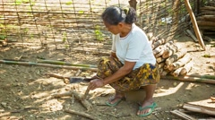 Luang prabang, laos - circa dec 2013: local woman makes a wooden peg with a m Stock Footage