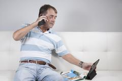Adult Male Multi-tasking, Reading and Talking on a Mobile Phone. Stock Photos