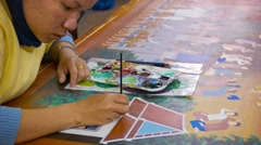 Siem reap, cambodia - 23 dec 2013: unidentified young woman paint on silk. si Stock Footage